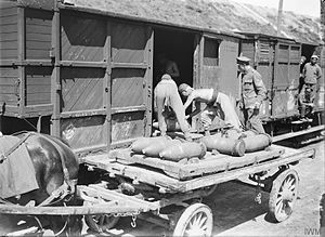 Chinese Labour Corps - CLC men load 9.2-inch shells onto a railway wagon at Boulogne for transport to the front line, August 1917
