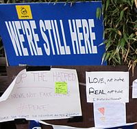 "Signs reading ""We're still here"", ""Love, not hate / Real, not fake"" and other messages"
