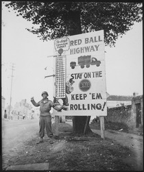 """Corporal Charles H. Johnson of the 783rd Military Police Battalion, waves on a """"Red Ball Express"""" motor convoy... - NARA - 531220.tif"""
