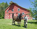 Cowboy with horse in front of barn house.jpg
