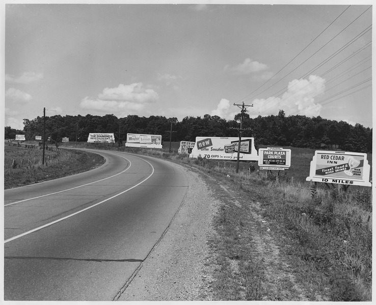 Curve in highway with assorted billboards - NARA - 283530