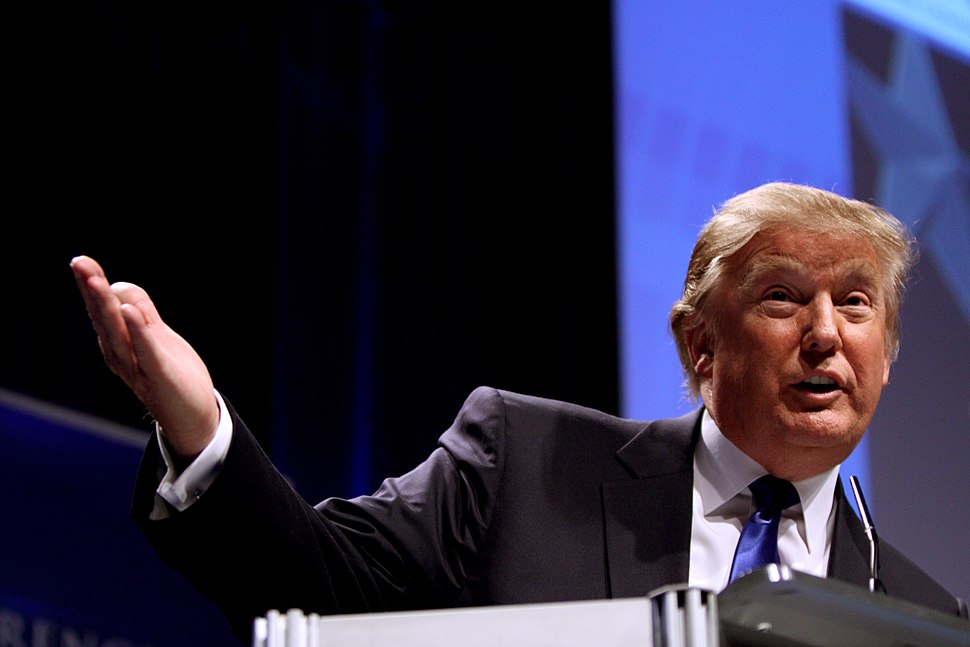 Donald Trump, dressed in a black suit with white shirt, and blue tie. He is facing toward the viewer and speaking at the Conservative Political Action Conference in February 2011.