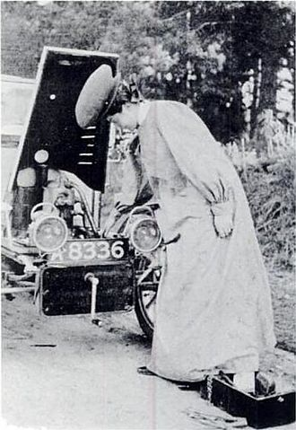 Car coat - Dorothy Levitt priming a carburettor and wearing an early version of a motoring 'duster' coat