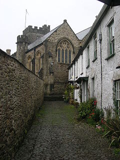 Stone building with arched windows and square tower seen at the end of a narrow lane with white painted houses on the right and a wall on the left