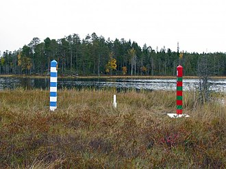 Finland–Russia border - The easternmost point of Finland is the western part of an island in Lake Virmajärvi, divided by the border. The white and blue striped pole on the left represents the Finnish border zone, while the red and green striped pole on the right represents the Russian border zone. The short white pole in the middle marks the actual border.