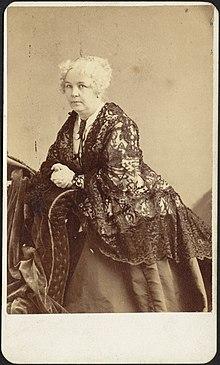 Foto von Elizabeth Cady Stanton, die sich an ein Möbelstück lehnt und sich der Kamera zuwendet