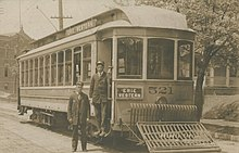 Erie Western Electric Railway car in Toledo, Ohio with one man standing in entrance to car while another stands on the ground next to the car.