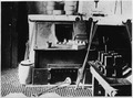 Front View of Melting Furnace, Showing Crucible, Dipping Cup, Stirrer, Tongs, Ingot Molds, Metal Bars, Etc. - NARA - 296574.tif