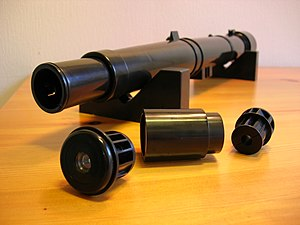 Galileoscope - At the front, left: The four-lens main eyepiece. Middle: Barlow tube. Right: The two lens auxiliary eyepiece. Background: The focus tube and main telescope tube containing the achromatic doublet objective lens.