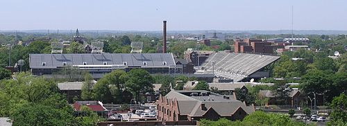 "An elevated view of several buildings and the trees surrounding them. A red brick building with a sloped roof is in the foreground, and a large white football stadium is just behind it, taking up much of the center of the picture. Beyond the stadium, there is a red brick smokestack near the center of the picture, the red brick Tech Tower building on the left side bearing white letters that spell ""TECH"", and the red brick physics building on the right side. In the background there is a white domed building. All around these buildings are green-leafed oak trees. An overcast, light blue sky takes up the top third of the picture."