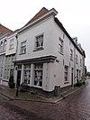 foto van Huis op de hoek van de St.Jorisstraat, met simpele witgepleisterde lijstgevels