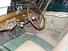 Photo de l'intérieur d'une voiture, la planche de bord est en metal peint en brun et la sellerie est faite de tweed.