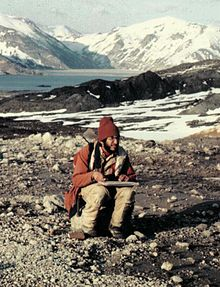 Man wearing a coat and hat and holding a pad of paper sits on a rock , with a lake and several mountains visible in the background