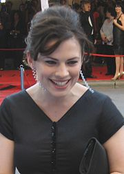 Woman in black dress, with pearl earrings and hair tied up
