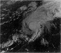 A satellite image of a hurricane. The storm has strong thunderstorm development around its small center and Bermuda is completely obscured by it