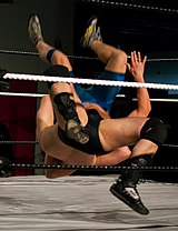 Behind ropes, only legs and a hand are visible of two grappling men.