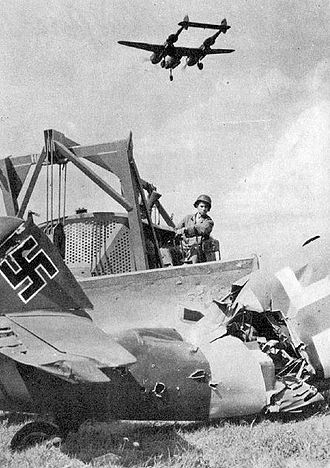 Advanced Landing Ground - A USAAF Engineer clearing out the wreckage of a destroyed Luftwaffe Bf 109 aircraft at an ALG, with a P-38 Lightning flying overhead on landing approach