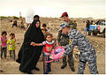 Iraqi police hand a backpack to a girl in the Kadhamiyah neighborhood of Baghdad, Iraq, June 7, 2011 110607-A-ZF802-074.jpg