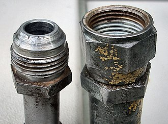 JIC fitting - JIC hydraulic fitting from 1967 Ford backhoe. It was badly stuck, but shows what a JIC fitting looks like. The left is the male part, the right is female.
