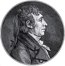 A man with long, braided hair wearing a high-collared, white shirt and dark jacket