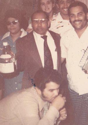 Mama Juana - Rodriguez (left) and Tatico Henriquez (right) holding a glass jug of home-made Mama Juana