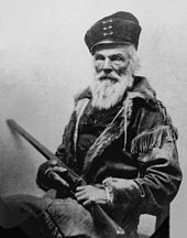 Elderly man with bear and hat holding a long barrel gun