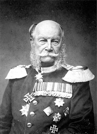 Iron Cross - King Wilhelm I of Prussia wearing the 1813 Iron Cross 2nd class (with ribbon) and 1870 Iron Cross 1st class (on his chest). The larger Grand Cross (in his buttonhole), awarded in 1871, was the precursor to the Knight's Cross worn around the neck.