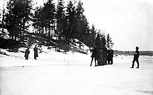 A firing squad of the Whites is executing two Red soldiers with rifles in wintry field against a small hill. The leader of White unit is standing behind the firing squad.
