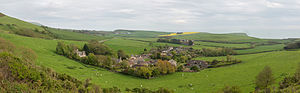 Kimmeridge - A panoramic view of the village from the north, looking towards the English Channel coast, which forms the horizon. The slopes of Smedmore Hill are to the left, and the Clavell Tower can just be seen on the step-shaped hill above and to the right of the village. The small parish church is on the left edge of the main cluster of buildings. Kimmeridge civil parish covers the village and the land beyond and to the left; the land in the foreground, between the camera and village, is part of neighbouring Steeple parish.