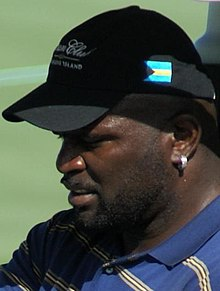 A man in a blue shirt with gray, white, and black stripes, wearing a black baseball cap.