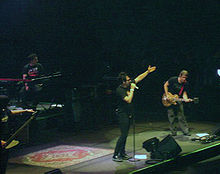 Four people. On the far left a man with a low hand. Mounted on a platform a man sits on a bench with a keyboard in front. In the center a man standing, wearing black with his left hand and taking a microphone with his right hand extended. On the far right a man semi-inclined holding a guitar.