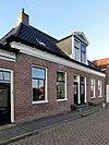 foto van Dubbel woonhuis onder breed schilddak met hoekschoorstenen met dubbele driezijdig bekroonde dakkapel met kleine klauwstukken