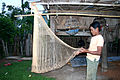 Laos - Katang man fixes fishing net.jpg