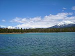 View to the northeast across Lava Lake with three volcanic mountains in the background: South Sister, Broken Top, and Mount Bachelor.