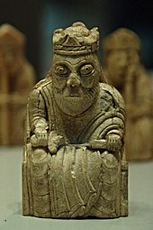 Photograph of an ivory gaming piece depicting a seated king
