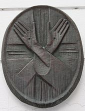 An oval wooden structure, with two hands etched in it in a cross. Both the hands show a small hole in the middle of the palm.