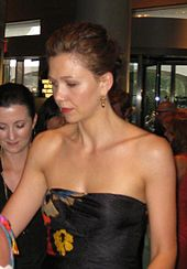 A brown haired woman looking away from the camera. Her hair is tied back, and she is wearing gold earrings and a shoulderless, sleeveless black dress with a yellow, red, and blue patten