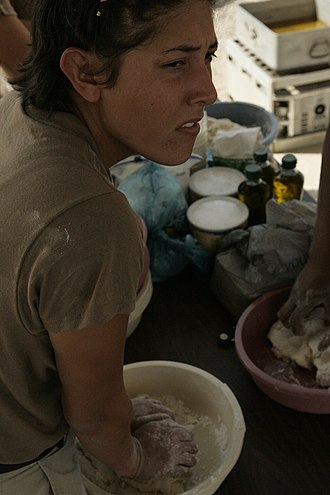 Muscogee (Creek) Nation - Spc. Stacy R. Mull, an enrolled Creek from Okemah, makes frybread at a powwow at Camp Taqaddum, Iraq, 2004.