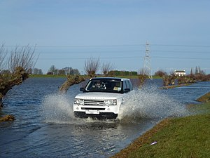 Washland - Car on the A1040 crossing flooded Whittlesey Wash, part of the Nene Washes