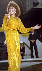 A woman with long brown hair wearing a long gold dress, singing into a microphone