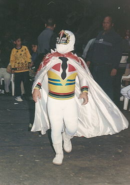 a dwarf dressed in a white body suit and mask, wearing a colorful cape, walking through a crowd of people.