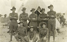 A portrait of several soldiers wearing upturned slouch hats in front of a tent during a training camp