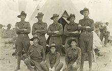 Ein Portrat von mehreren Soldaten, die wahrend eines Trainingslagers umgedrehte Schlapphute vor einem Zelt tragen