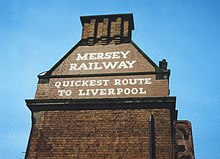 "A painted sign on the side of a building with the following text in capital letters: ""Mersey Railway"" ""Quickest route to Liverpool""."