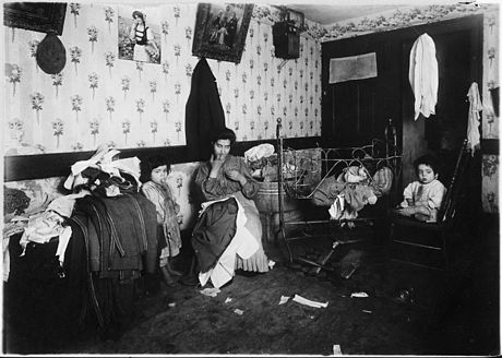 Italian immigrant woman working in her home, New York City in 1912 Mrs. Guadina, living in a dirty, poverty stricken home. On the trunk is the work of 4 days. She was struggling along... - NARA - 523517.jpg