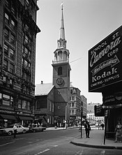 On a city street, an old brick church with a tall steeple is surrounded by modern buildings.