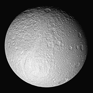Tethys (moon) - Cassini view of Tethys's Saturn-facing hemisphere, showing the giant rift Ithaca Chasma, crater Telemachus at top, and smooth plains at right