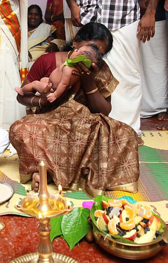 Sanskara (rite of passage) - A new born's Namakarana ceremony. The grandmother is whispering the name into the baby's ear, while friends and family watch.