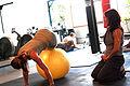 Personal trainer monitoring a client's movement during a fitball exercise.JPG