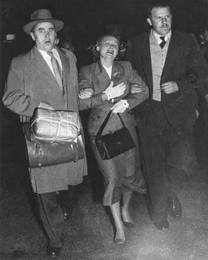 Petrov Affair - Evdokia Petrova at Mascot Airport, Sydney, being escorted across the tarmac to a waiting plane by two armed Soviet diplomatic couriers (19 April 1954).